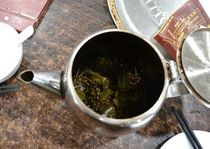 A metal teapot filled with loose leaf tea