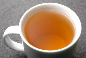 A cup of tea with a light golden color