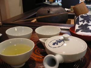 Green tea in a traditional Japanese cup with other teaware nearby