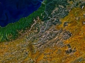Satellite photo showing water in the top left, a green area, and mountains followed by a drier area to the southeast.