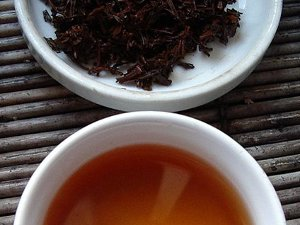 Wet black tea leaves with a dark brown color, and brewed tea liquor below