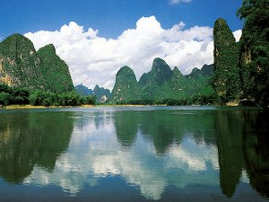 A river with tall, round-top mountains rising behind it