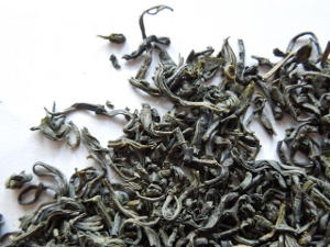 Loose leaf chun mee, showing small gray-green, slightly curved tea leaves