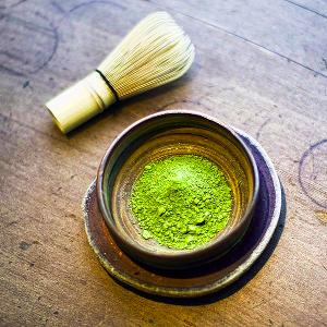 A bowl with matcha powder, and a whisk for preparation on the side