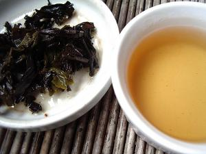 A cup of oolong tea with a golden color, and used tea leaves on the left