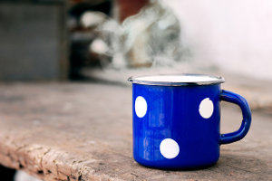 A blue polka dot mug with something steaming hot in it