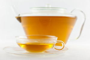 A cup and glass teapot of tea with a light golden color