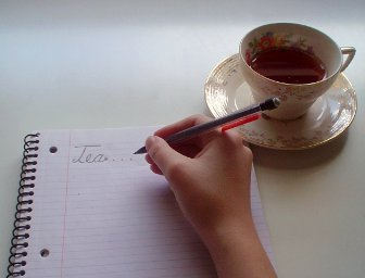Cup of Tea and Hand Writing Tea in a Notebook