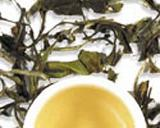 Green Tea Leaves and Cup of Light Yellow Tea