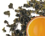 Dark Green Curled Tea Leaves with Golden-colored Cup of Tea
