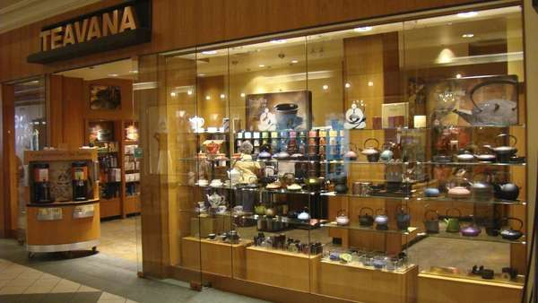 Teavana mall storefront, with glass display case of teapots, doorway, and store behind