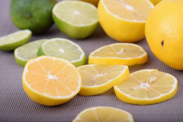 Several thin yellow lemon slices and a few green lime slices, and a whole lemon and lime, on a gray background