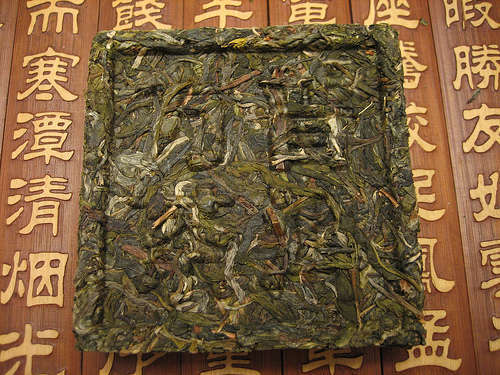 Green tea leaves compressed into a square shape with Chinese characters printed on it, against a wooden background with Chinese characters