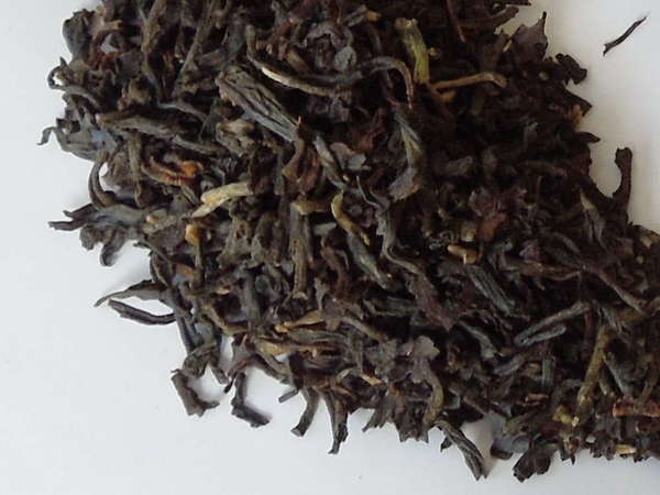 Loose-leaf black tea with mostly black and dark-brown colors, a few greenish-olive leaves