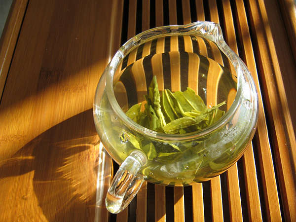 Large green tea leaves steeping in a glass pitcher, on a wooden grate