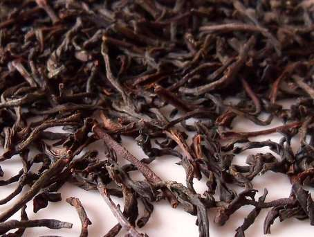 Long, wiry, twiggy-looking tea leaves with black to reddish-olive colors