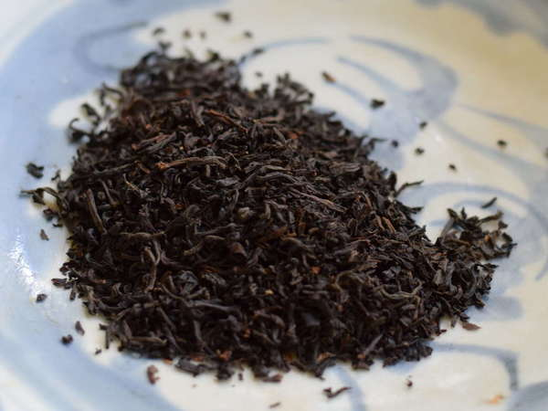 Fine-textured loose-leaf black tea on a pale blue-and-white plate