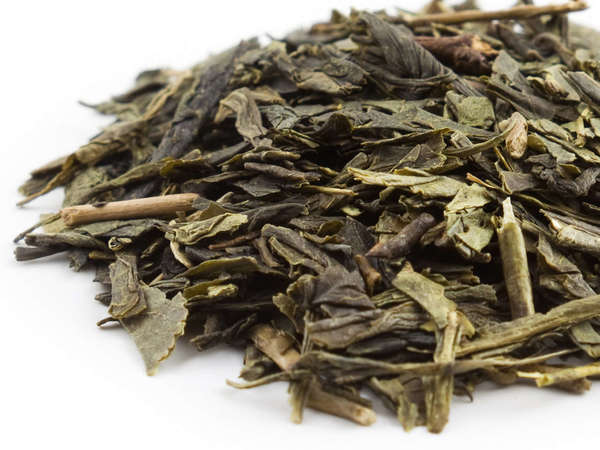 Loose-leaf green tea with dark green, flat leaves, slightly broken, and a few stems