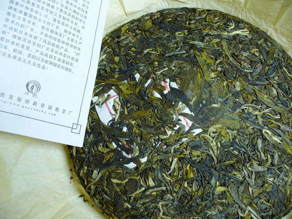 Round, compressed tea cake with varying shades of green leaf, pamphlet with Chinese characters on left
