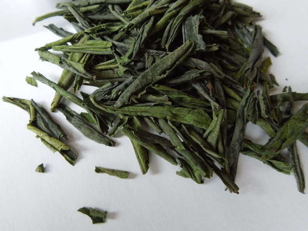 Loose-leaf green tea with straight, somewhat rolled leaves, vibrant green in color
