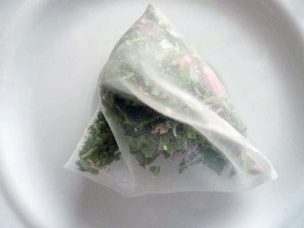 Pyramid-shaped tea bag filled with fine pieces of green leaves and lavender flowers