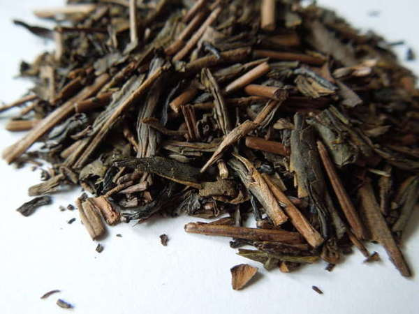 Long, flat, flakey, dark brown tea leaves with a wooden-looking color and texture