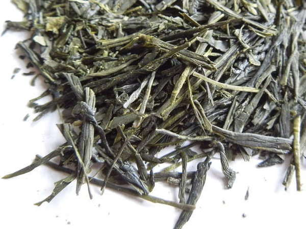 Loose-leaf green tea showing intact long, flat, pointy leaves with dark green color