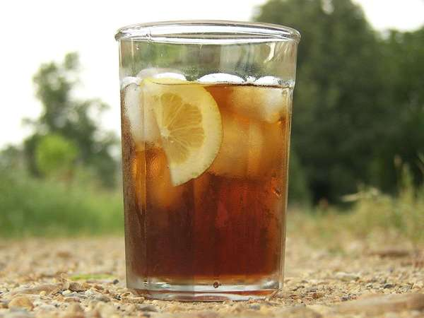Large glass of iced black tea with lemon and ice cubes, on gravel with blurred green background