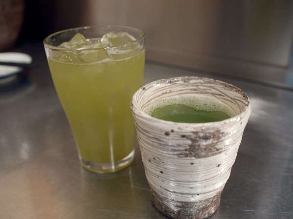 Ceramic cup with hot green tea on right, glass of iced green tea on left, paler yellow in color