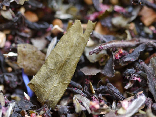 Colorful loose-leaf flavored tea blend with black tea leaves, blue and purple flowers, and large olive-green dried leaves