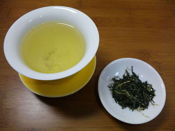 Brewed cup of tea with golden-green color top left, dish with dark green loose-leaf tea lower right