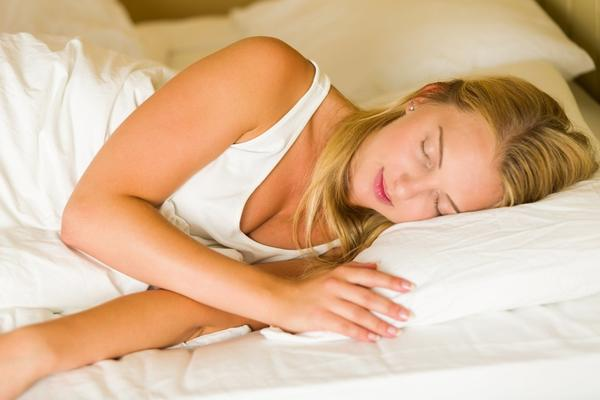 A blonde white woman sleeping on a bed with white beddings