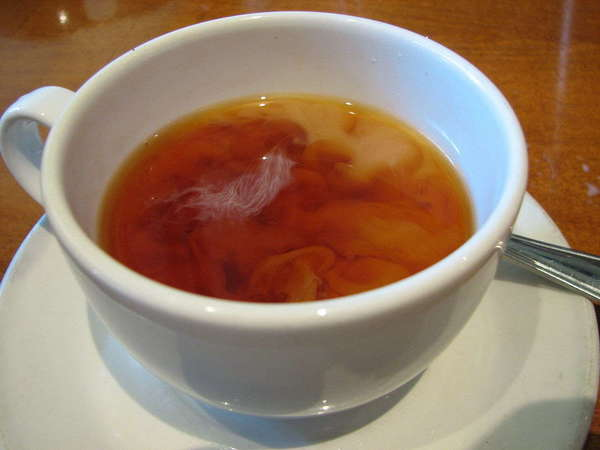 A white cup on a white saucer, filled with reddish-brown tea with swirling cloud shapes from added milk