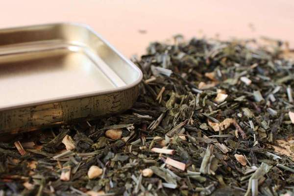 Upside down square metal tea tin lid, loose-leaf dried herbs showing dark gray-green leaf and straw-colored stem