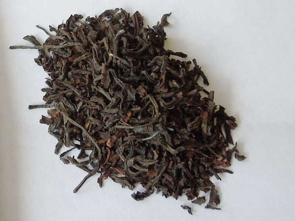 Black tea leaves with some reddish-olive hues, slightly curved, a few slightly broken pieces
