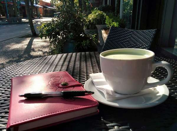 Closed journal with pen on top, cup of foamy green tea, on table along a street