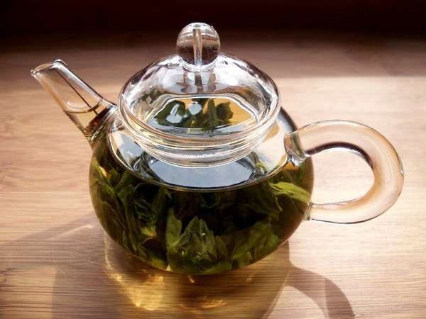 Glass teapot filled with large-leaf green tea leaves, on wooden background