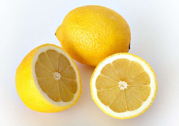 Two lemons, one whole, one sliced showing two cross-sections, on a white background