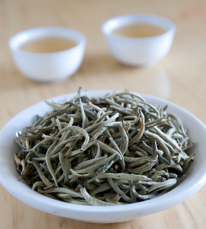 Loose leaf tea consisting of silver-green tips in a white dish, two blurry cups of pale yellow tea in background