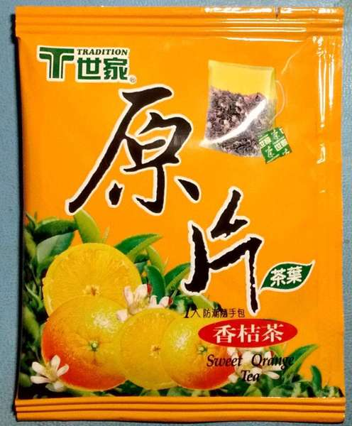 Bright orange teabag wrapper with oranges and tea leaves, reading sweet orange tea, Tradition brand, and Chinese characters