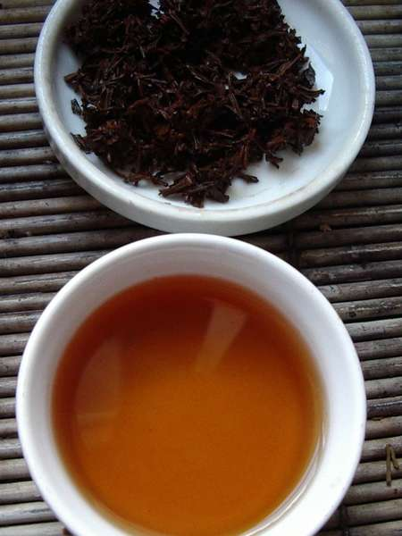 Cup of brewed black tea below, wet (used) black tea leaves on dish above