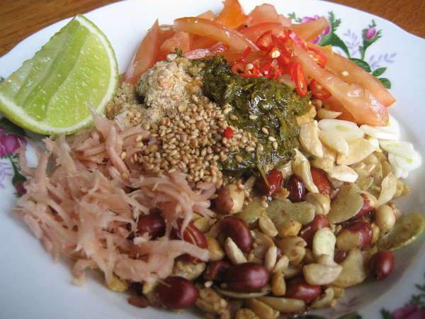 A plate with a lime slice, pickled tea leaves, various beans and seeds, and other veggies