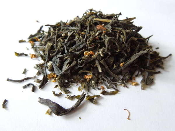 Tea with dark olive-green leaves, many broken, and a few small orange dried flowers mixed in