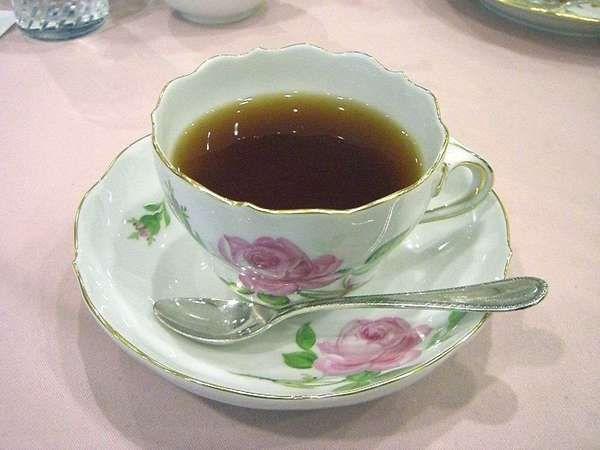 Victorian rose-patterned tea cup filled with black tea, with matching saucer and shiny spoon, on a pink background