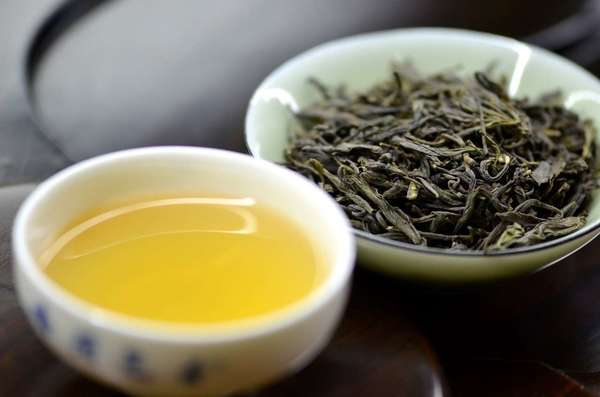 Cup of yellow-colored tea on left, dish of gray-green tea leaves on right