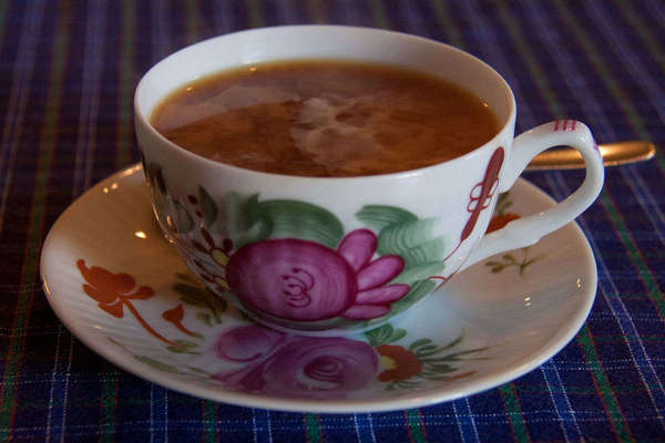 Black tea with swirling milk in a rose-patterned teacup on matching saucer, on blue plaid tablecloth