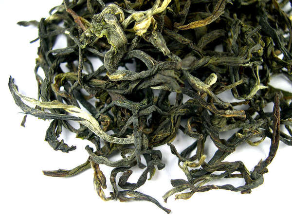 Loose-leaf oolong tea with dark green, twisted leaves, a few silvery-golden