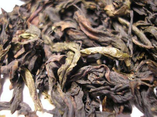 Closeup of tea leaves showing twisted, wrinkly shapes, colors ranging from dark reddish-brown to light olive-green