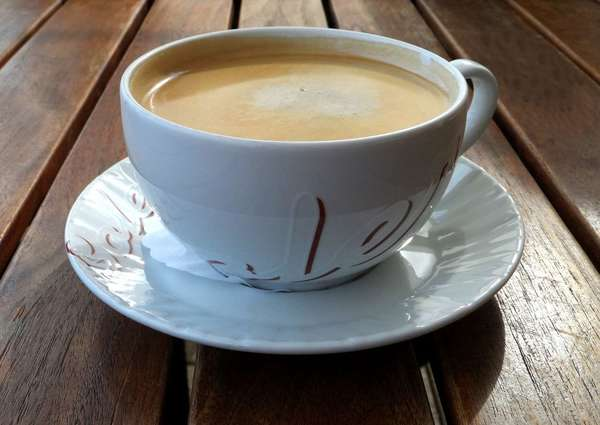 Cup of coffee with milk, foamy appearance, in saucer, on dark wooden table with space between slats
