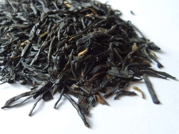 Loose-leaf black tea with long, wiry black leaves and a few golden tips